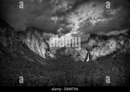 Black and White tunnel View during a clearing storm with the moon rising - Stock Photo