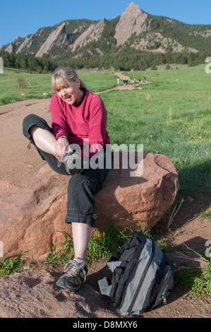 Woman rubbing hurt ankle. - Stock Photo