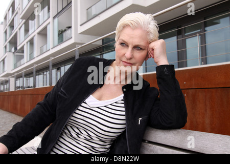 white haired woman sitting on a bench - Stock Photo