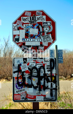 A stop sign which has been covered by stickers and graffiti in brooklyn new york