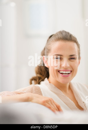 Portrait of happy young housewife in living room - Stock Photo