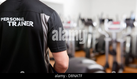 Personal Trainer, with his back facing the camera, looking at a gym - Stock Photo