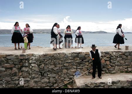 Local people meeting tourists on the pier of Amantani Island, Lake Titicaca, Peru, South America - Stock Photo