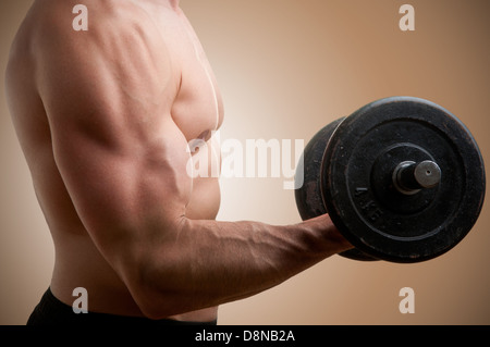 Personal Trainer doing standing dumbbell curls for training his biceps - Stock Photo