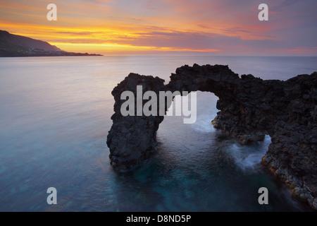 Natural Arch of Fajã da Ribeira da Areia at sunset with Fajã do Ouvidor at the horizon - São Jorge - Azores - Stock Photo
