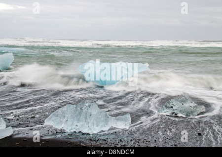 Icebergs washed up on black sand beach, Jökulsárlón glacial lagoon, Iceland - Stock Photo