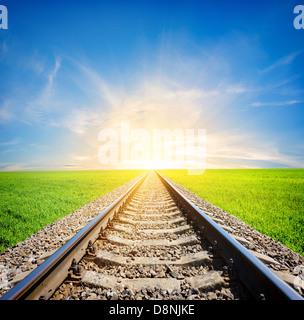 Railway to the sun through green field - Stock Photo