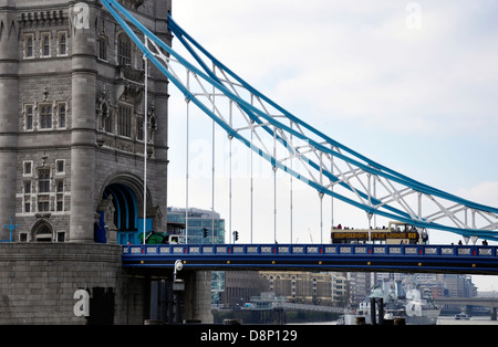 Close-up of the historic landmark, Tower Bridge, with Thames river view and a London tour bus crossing the bridge. - Stock Photo