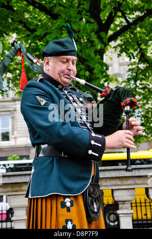 2nd June 2013, Belfast, Northern Ireland.  A piper plays a lament on bagpipes at Belfast City Hall, to commemorate - Stock Photo