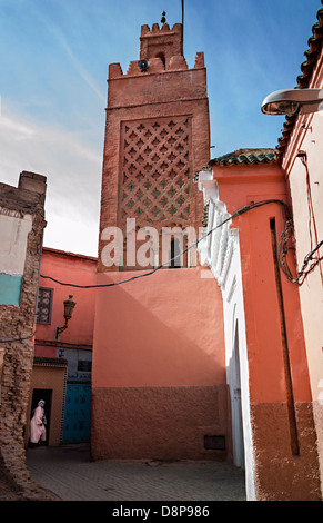 Woman in doorway below decorative Arabic minaret, colorful buildings with blue sky, Marrakesh Morocco - Stock Photo