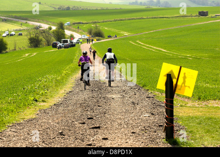 Two cyclists head towards runners on the Three Forts Challenge on the South Downs way in West Sussex. - Stock Photo
