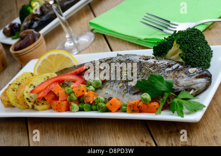 Dish with baked trout and vegetables on the kitchen table - Stock Photo