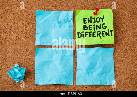 enjoy being different advice - lifestyle or nonconformist concept - handwriting on colorful sticky notes - Stock Photo