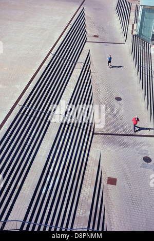 Looking down to a man walking and a man  running along a path through steps creating a strange perspective - Stock Photo