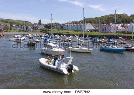 A family on a motor boast in Aberaeron Harbour, Ceredigion, Wales, UK - Stock Photo