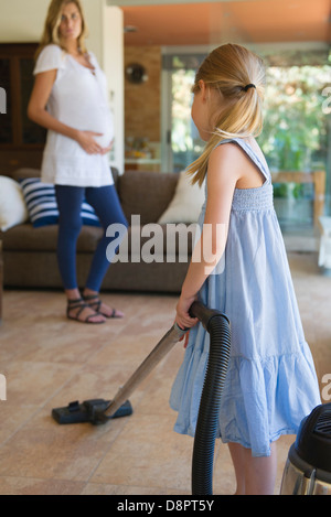 Little girl vacuuming, pregnant mother in background - Stock Photo