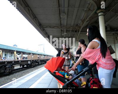 Family waiting for train on railway station platform Cardiff Central Station in Wales UK   KATHY DEWITT - Stock Photo