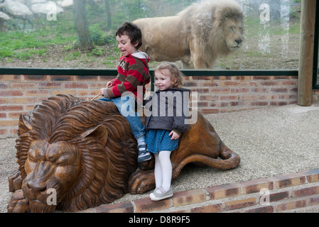 Children playing on lion statue in front of lion enclosure at the zoo - Stock Photo