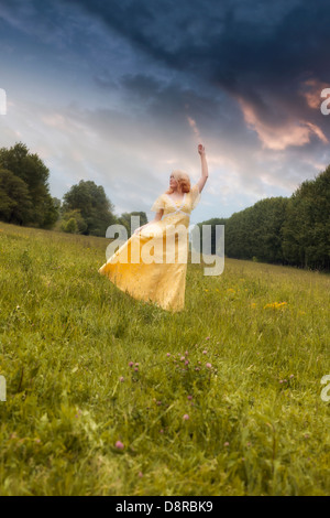 a girl in a yellow dress is dancing on a meadow - Stock Photo