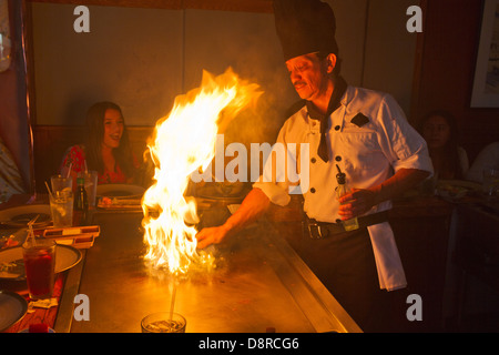 A chef prepares Japanese barbecue on a griddle with flames shooting up as excited young women look on. - Stock Photo