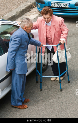 Overhead view of elderly couple / woman with walking frame getting into car - France. - Stock Photo