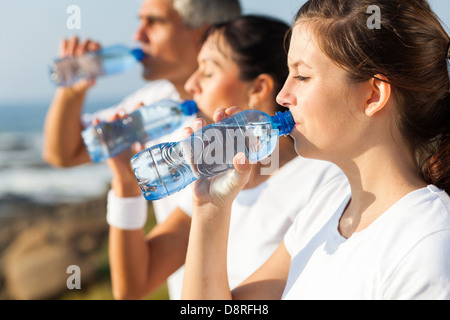 active family drinking water after jogging in the morning - Stock Photo