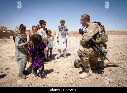 US Army Staff Sgt. Matthew Parsons with the Police Adviser Team Delaram talks with Afghan children May 26, 2013 - Stock Photo