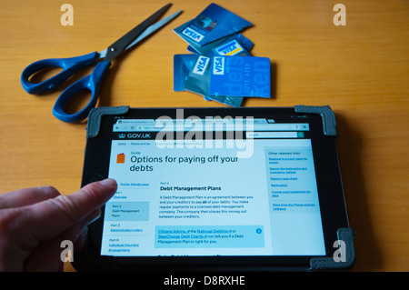 Person looking into UK debt relief information on internet on ipad mini tablet computer at home - Stock Photo