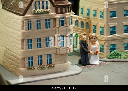 Looking through window of cake shop at decorated cake of bride and groom standing in front of bridge of Sighs at - Stock Photo