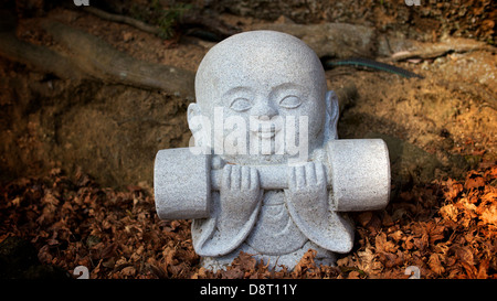 Small stone statue of a little monk lifting a weight at Daishoin Temple in Miyajima - Stock Photo