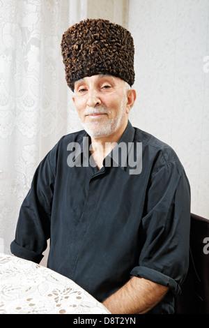 Senior man sitting at table - Stock Photo