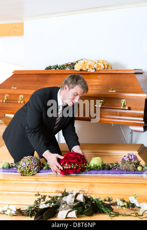 Undertaker in his store with a display of coffins - Stock Photo
