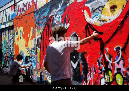 Youngsters with spray cans in alley spraying colourful graffiti on wall of building in town - Stock Photo