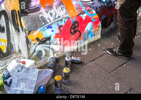 Spray cans on the ground and youngster spraying colourful graffiti on wall of building in city - Stock Photo
