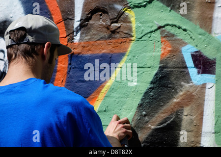 Youngster with spray can in alley spraying colourful graffiti on wall of building in town - Stock Photo