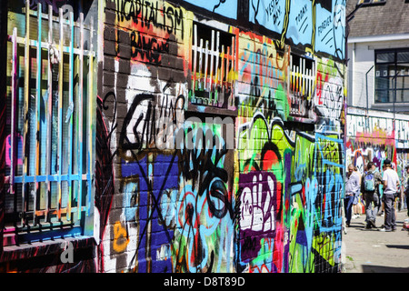 Youngsters in alley spraying colourful graffiti on wall of building in city - Stock Photo