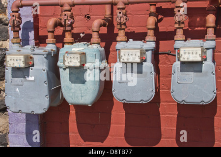 A line of four, old utility meters on a colorful wall - Stock Photo