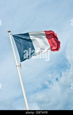 The French Tricolour flag flying atop a flagpole - Stock Photo