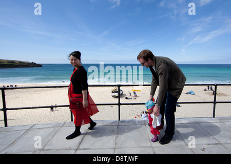 A family takes a stroll on the seafront where TATE St Ives overlooks Porthmeor Beach - Stock Photo