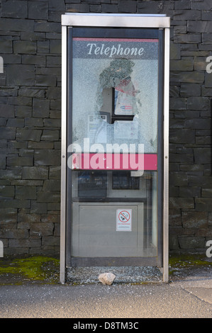 A vandalized   telephone box that has had it's glass smashed with a rock, which is seen laying on the ground - Stock Photo
