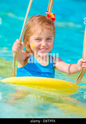 Cute happy baby girl enjoying summer holiday in the pool, having fun on water swing, red frangipani flower in hair, - Stock Photo