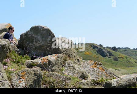 A young man looks out over the landscape at Herm in the Channel Islands - Stock Photo
