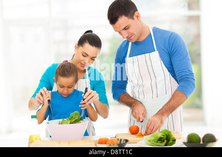 mother teaching little daughter mixing salad when family cooking in kitchen - Stock Photo