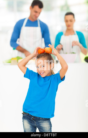 little girl having fun with tomatoes while her parents cooking in kitchen - Stock Photo
