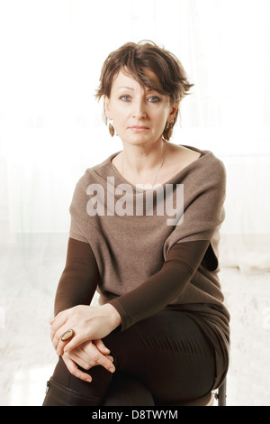Serious middle aged woman in brown sweater - Stock Photo