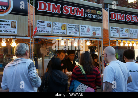 People buying Dim Sum snacks at a street food stall at the night market in Chinatown, British Columbia, Canada - Stock Photo