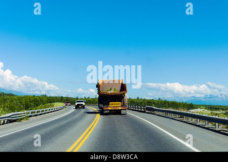Construction vehicle, oversize, wide load, traveling south on Highway 3, north of Anchorage, Alaska, USA - Stock Photo