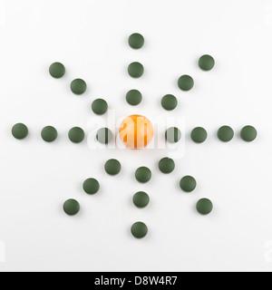 Fresh Golden berry (Physalis peruviana) and Chlorella tablets, broken wall single cell green algae - Stock Photo