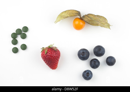 Fresh golden berry, strawberry, blueberries and Chlorella tablets - Stock Photo