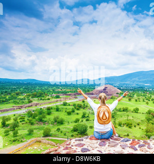 Back side of tourist girl sitting with raised up hands on the top of mountains and enjoying view of Mexican pyramid, - Stock Photo
